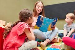 Μπέιμπι-σίτερ και παιδιά που διαβάζουν μεγαλοφώνως στοκ φωτογραφία με δικαίωμα ελεύθερης χρήσης