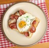 Μπέϊκον και τηγανισμένο αυγό στη φρυγανιά Στοκ Εικόνες