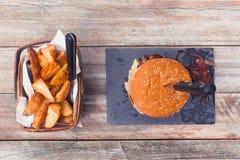 Μπέϊκον τυριών burger και πατατών περικοπές, τοπ άποψη Στοκ Εικόνες