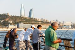 Μπακού, Αζερμπαϊτζάν - 16 Ιουλίου 2015: Ψαράδες στη Κασπία Θάλασσα στα πλαίσια της πόλης του Μπακού Στοκ φωτογραφία με δικαίωμα ελεύθερης χρήσης