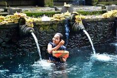 ΜΠΑΛΙ, ΙΝΔΟΝΗΣΙΑ - 18 ΜΑΐΟΥ Γυναίκα στο νερό Pura Tirta Empul ελαιόπρινου στις 18 Μαΐου 2016 στο Μπαλί, Ινδονησία ΜΠΑΛΙ, ΙΝΔΟΝΗΣΙ Στοκ Φωτογραφία