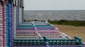 Μπαλκόνια καλυβών παραλιών σε μια κενή παραλία που αγνοεί το αιολικό πάρκο στην Αγγλία πριν από τη θύελλα στοκ φωτογραφίες