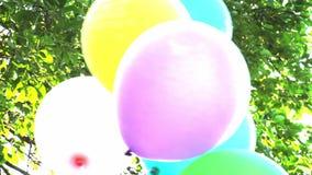 μπαλονιών Χρόνια πολλά ζωηρόχρωμα μπαλόνια στο υπόβαθρο του ουρανού και του φυλλώματος σε αργή κίνηση φιλμ μικρού μήκους