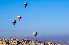 Μπαλόνια ζεστού αέρα που πετούν πέρα από το σεληνιακό τοπίο Goreme σε Cappadocia, Τουρκία Στοκ Φωτογραφίες