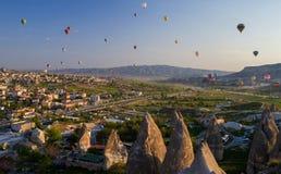 Μπαλόνια ζεστού αέρα στην ανατολή που πετούν πέρα από Goreme Cappadocia, Τουρκία Στοκ Φωτογραφίες