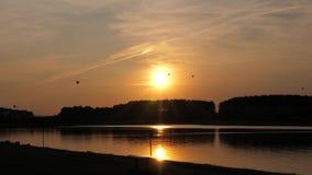 Μπαλόνια στο σκηνικό του ήλιου ρύθμισης και της λίμνης απόθεμα βίντεο