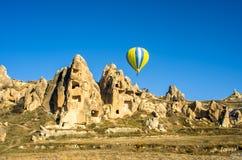 Μπαλόνι ζεστού αέρα που προεξέχει τις αρχαίες κατοικίες Cappadocia, Τουρκία Στοκ εικόνες με δικαίωμα ελεύθερης χρήσης