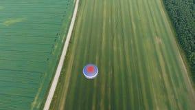 Μπαλόνι ζεστού αέρα στον ουρανό πέρα από έναν τομέα Στοκ Φωτογραφία