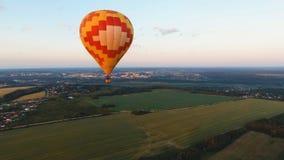 Μπαλόνι ζεστού αέρα στον ουρανό πέρα από έναν τομέα Στοκ Φωτογραφίες