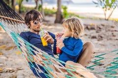 Μπαμπάς και γιος που έχουν τη διασκέδαση σε μια αιώρα με ποτά στοκ φωτογραφία