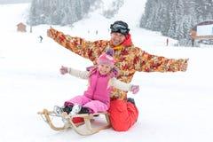 Μπαμπάς και κόρη που θέτουν τη συνεδρίαση σε ένα έλκηθρο το χειμώνα Στοκ εικόνες με δικαίωμα ελεύθερης χρήσης