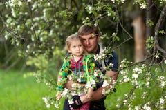 Μπαμπάς και κόρη στα ανθίζοντας δέντρα Στοκ Εικόνα