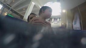 Μπαμπάς και λίγος γιος που κολυμπούν στην εσωτερική λίμνη απόθεμα βίντεο