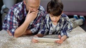 Μπαμπάς και ο γιος του που μαθαίνουν πώς να χρησιμοποιήσει τη νέα ταμπλέτα, σύγχρονη τεχνολογία, στενότητα στοκ εικόνες