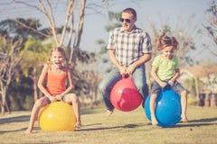 Μπαμπάς και παιδιά που παίζουν στο χορτοτάπητα μπροστά από το σπίτι Στοκ Εικόνες