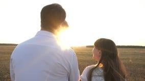 Μπαμπάς και περίπατος Mom με την κόρη της στα όπλα της στο ηλιοβασίλεμα οικογενειακοί περίπατοι με ένα παιδί στο ηλιοβασίλεμα πατ απόθεμα βίντεο