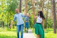 Μπαμπάς και mom αυξημένος την άνω πλευρά γιων τους και περπάτημα κατά μήκος του πάρκου π Στοκ Φωτογραφία