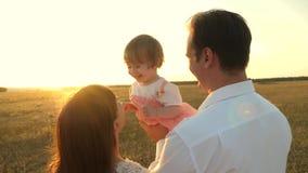 Μπαμπάς και mom παιχνίδι με μια μικρή κόρη στα όπλα της στο ηλιοβασίλεμα οικογενειακοί περίπατοι με ένα παιδί στο ηλιοβασίλεμα πα απόθεμα βίντεο