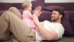 Μπαμπάς με τα χέρια παιχνιδιού μωρών Χαμογελώντας παιχνίδι κοριτσιών πατέρων και μικρών παιδιών με τα χέρια απόθεμα βίντεο