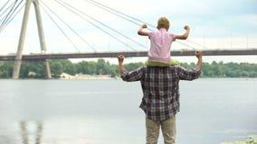 Μπαμπάς με το γιο στους ώμους του που εξετάζει την πόλη, που παρουσιάζει τη δύναμη και εμπιστοσύνη απόθεμα βίντεο