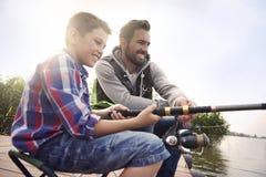 Μπαμπάς με το γιο του που αλιεύει από κοινού Στοκ εικόνες με δικαίωμα ελεύθερης χρήσης