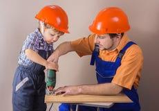 Μπαμπάς με το νέο γιο στο προστατευτικό λειτουργώντας τορνευτικό πριόνι κρανών Στοκ φωτογραφία με δικαίωμα ελεύθερης χρήσης