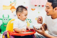 Μπαμπάς πατέρων που τρώει το γιο αγοράκι τροφών στοκ εικόνα