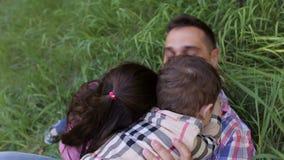 Μπαμπάς που έχει τη διασκέδαση με τα παιδιά στη χλόη στο πάρκο φιλμ μικρού μήκους