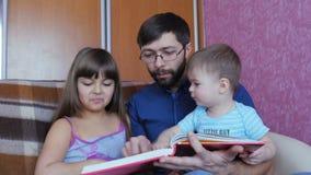 Μπαμπάς που διαβάζει ένα βιβλίο παιδιών ` s στα παιδιά του απόθεμα βίντεο