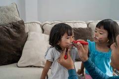 Μπαμπάς που κάνει κάποια ζωγραφική προσώπου στα πρόσωπα της κόρης στοκ φωτογραφία