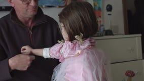 Μπαμπάς που ντύνει επάνω την κόρη ως ρόδινη νεράιδα σε αργή κίνηση SF φιλμ μικρού μήκους