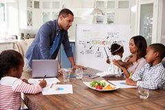 Μπαμπάς που παρουσιάζει την εσωτερική συνεδρίαση στην οικογένειά του στην κουζίνα Στοκ φωτογραφία με δικαίωμα ελεύθερης χρήσης