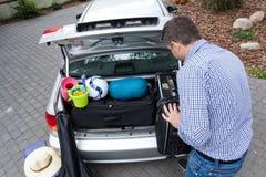 Μπαμπάς που προετοιμάζει τον κορμό αυτοκινήτων για τις διακοπές Στοκ Εικόνα
