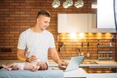 Μπαμπάς που προσπαθεί να εργαστεί στεμένος με το νεογέννητο babe του στο εσωτερικό Υπουργείων Εσωτερικών Στοκ εικόνα με δικαίωμα ελεύθερης χρήσης