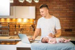 Μπαμπάς που προσπαθεί να εργαστεί στεμένος με το νεογέννητο babe του στο εσωτερικό Υπουργείων Εσωτερικών Στοκ φωτογραφίες με δικαίωμα ελεύθερης χρήσης
