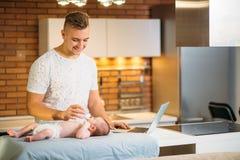 Μπαμπάς που προσπαθεί να εργαστεί στεμένος με το νεογέννητο babe του στο εσωτερικό Υπουργείων Εσωτερικών Στοκ Φωτογραφία