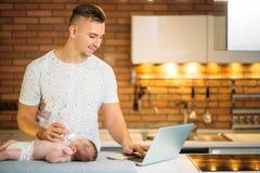 Μπαμπάς που προσπαθεί να εργαστεί στεμένος με το νεογέννητο babe του στο εσωτερικό Υπουργείων Εσωτερικών Στοκ Εικόνα