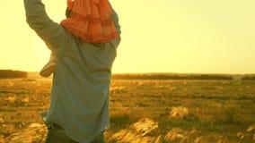 Μπαμπάς που χορεύει στους ώμους του με την κόρη του στον ήλιο Ταξίδια πατέρων με το μωρό στους ώμους του στις ακτίνες του ηλιοβασ απόθεμα βίντεο