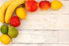 Μπανάνα, αχλάδι, ασβέστης, μήλα και λεμόνια στη γωνία στο ξύλινο υπόβαθρο Στοκ Φωτογραφίες