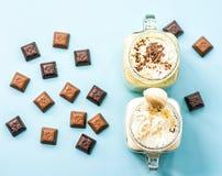Μπανάνα δύο και ακτινίδιο milkshakes στα βάζα κτιστών με creme στην κορυφή που διακοσμείται με τα κομμάτια σοκολάτας διεσπαρμένα  στοκ εικόνα
