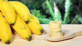 Μπανάνα στον ξύλινο πίνακα, που τεμαχίζεται στο ξύλινο κουτάλι, υπόβαθρο μπαμπού απόθεμα βίντεο