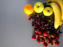 Μπανάνα, φράουλα, κεράσι, πορτοκάλι και μήλο σε ένα γκρίζο υπόβαθρο Στοκ φωτογραφία με δικαίωμα ελεύθερης χρήσης