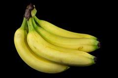 Μπανάνες σε μια μαύρη ανασκόπηση Στοκ Εικόνες