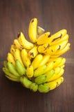 Μπανάνες σε μια ξύλινη επιφάνεια Στοκ Εικόνες