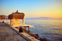 Μπανγκαλόου στη θάλασσα στο ηλιοβασίλεμα Ξύλινα περίπτερα στην ακτή μιας αμμώδους παραλίας - Bodrum, Τουρκία στοκ εικόνες
