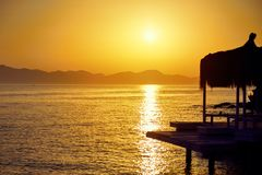 Μπανγκαλόου στη θάλασσα στο ηλιοβασίλεμα Ξύλινα περίπτερα στην ακτή μιας αμμώδους παραλίας - Bodrum, Τουρκία στοκ εικόνα