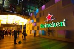 ΜΠΑΝΓΚΟΚ - 4 ΔΕΚΕΜΒΡΊΟΥ: Κόσμος λογότυπων επιλογής της Heineken κεντρικός τη νύχτα Στοκ Εικόνα