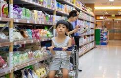 ΜΠΑΝΓΚΟΚ ΤΑΪΛΑΝΔΗ - 24 ΜΑΡΤΊΟΥ: Το μη αναγνωρισμένο αγόρι κοιτάζει επίμονα στην πλήξη σε ένα κάρρο αγορών όπως η μητέρα ψωνίζει σ στοκ φωτογραφία με δικαίωμα ελεύθερης χρήσης