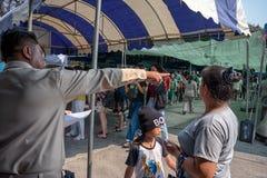 ΜΠΑΝΓΚΟΚ, ΤΑΪΛΑΝΔΗ - 17 ΜΑΡΤΊΟΥ: Ο αστικός εργαζόμενος βοηθά τους πολίτες στη σωστή γραμμή για να περιμένει στη σειρά για την εκλ στοκ εικόνες