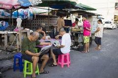 Μπανγκόκ, Ταϊλάνδη - 28 Ιουνίου 2015: Ηληκιωμένοι που διαβάζουν την εφημερίδα σε έναν στάβλο τσαγιού στην οδό της Μπανγκόκ στοκ εικόνα